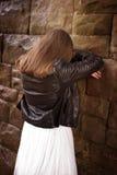Zurück von einer Jugendlichen, die an einer Wand sich lehnt Stockfotografie