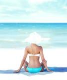 Zurück von einer jungen Frau in einem Badeanzug auf dem Strand Lizenzfreies Stockfoto