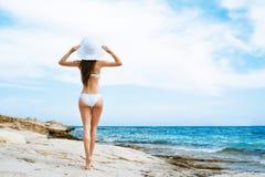 Zurück von einer jungen Frau in einem Badeanzug und in einem Hut auf dem Strand Stockbilder