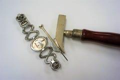 Zurück von einer silbrigen Uhr ist entfernt worden und liegt unter Reparaturwerkzeugen stockfotografie