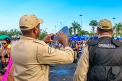 Zurück von zwei nehmenden Polizisten parken Bilder von Kostümleuten bei Bloco Orquestra Voadora in Flamengo, Carnaval 2017 Stockbilder