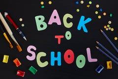 Zurück zu der Schulaufschrift gemacht von farbigen Buchstaben und von Schulbedarf auf dem schwarzen Hintergrund stockbild