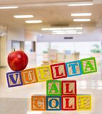 Zurück zu der Schule buchstabiert heraus auf spanisch mit Holzklötzen mit Apfel lizenzfreie stockfotografie
