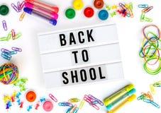 Zurück zu der Schule geschrieben in einen Leuchtkasten, bunter Schulbedarf auf Weiß stockfotografie