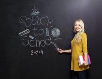 Zurück zu der Schullehrerin, die durch Tafel lächelt Stockbilder