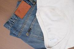 Zurück zu grundlegendem, blauem Baumwollstoff und einem weißen T-Shirt Stockfotografie