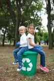 Zurück zu hinteren Kindern in den Jeans und in weißen kurzen Hosen, sitzend auf dem großen grünen Papierkorb mit weißem Aufkleber stockbilder