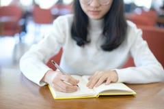 Zurück zu Schulbildungswissenscollege-Hochschulkonzept junge Geschäftsfrau, die bei Tisch sitzt und Kenntnisse im Notizbuch nimmt lizenzfreies stockbild