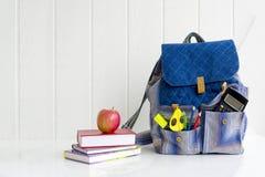 Zurück zu Schule Apple, Stapel von Büchern und von Rucksack auf dem Schreibtisch in der Schule Lizenzfreies Stockfoto
