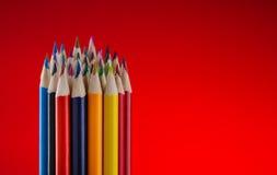 Farbbleistifte auf rotem Hintergrund Stockfoto