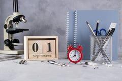 Zurück zu Schule Gruppe des Schulbedarfs, des roten Weckers, des Mikroskops und des hölzernen Kalenders mit Datum am 1. September Stockfotografie
