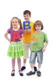 Zurück zu Schule - Kinder, die große ABC-Zeichen anhalten Stockbild