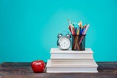 Zurück zu Schule-Konzept Bücher, farbige Bleistifte und Uhr Stockfotografie