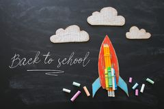 Zurück zu Schule-Konzept Draufsichtbild der handgemachten Papprakete und -wolken mit Bleistiften über Klassenzimmertafelhintergru stockfotos