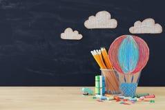 Zurück zu Schule-Konzept Heißluft Ballon und Bleistifte vor Klassenzimmertafel Lizenzfreies Stockfoto