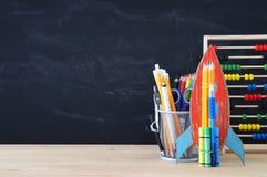 Zurück zu Schule-Konzept Papprakete und -bleistifte über offenem Buch vor Klassenzimmertafel Stockfotografie