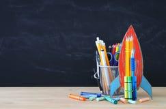 Zurück zu Schule-Konzept Papprakete und -bleistifte über offenem Buch vor Klassenzimmertafel Lizenzfreies Stockbild