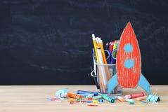Zurück zu Schule-Konzept Papprakete und -bleistifte über offenem Buch vor Klassenzimmertafel Stockbild