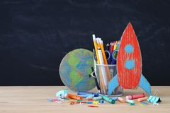 Zurück zu Schule-Konzept Papprakete und -bleistifte über offenem Buch vor Klassenzimmertafel Lizenzfreies Stockfoto