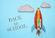Zurück zu Schule-Konzept Pappraketenschnitt vom Papier und über hölzernem blauem Hintergrund gemalt Stockbild