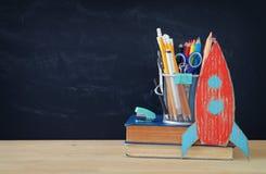 Zurück zu Schule-Konzept Rakete und Bleistifte über offenem Buch vor Klassenzimmertafel Stockfoto