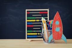 Zurück zu Schule-Konzept Rakete und Bleistifte vor Klassenzimmertafel Lizenzfreie Stockfotos
