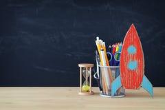 Zurück zu Schule-Konzept Rakete und Bleistifte vor Klassenzimmertafel Lizenzfreies Stockfoto
