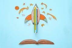 Zurück zu Schule-Konzept schnellen Sie hoch, der Raumelement-Formschnitt vom Papier und über hölzernem blauem Hintergrund gemalt Stockbild