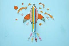 Zurück zu Schule-Konzept schnellen Sie mit Bleistiften hoch, der Raumelement-Formschnitt vom Papier und über hölzernem blauem Hin Lizenzfreie Stockfotografie