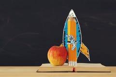 Zurück zu Schule-Konzept schnellen Sie Skizze und Bleistifte über offenem Buch vor Klassenzimmertafel hoch Stockfotos