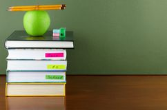 Zurück zu Schule - Lehrbücher und Apfel über hölzernem Schreibtisch Lizenzfreie Stockfotografie