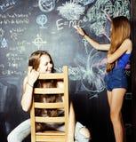 Zurück zu Schule nach Sommerferien, zwei jugendlich Mädchen im Klassenzimmer mit der Tafel zusammen gemalt lizenzfreie stockbilder