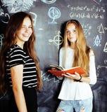 Zurück zu Schule nach Sommerferien, zwei jugendlich wirkliche Mädchen im Klassenzimmer mit der Tafel zusammen gemalt, Lebensstil lizenzfreie stockfotos
