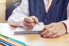 Zurück zu Schule Nettes Kind, das am Schreibtisch im Klassenzimmer sitzt Junge lernt, dass Lektionen einen Stift in ein Notizbuch lizenzfreie stockfotos