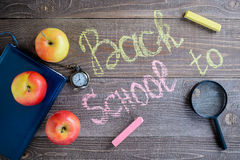 Zurück zu Schulezubehör Buch, Äpfel und Uhr auf einem hölzernen Hintergrund Lizenzfreie Stockfotos