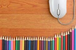 Farbbleistifte und eine Computer-Maus Stockfoto