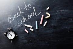 Zurück zu Schulhintergrund auf Tafel mit bunten Kreiden und Wecker Lizenzfreie Stockfotos