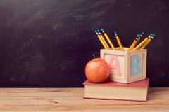 Zurück zu Schulhintergrund mit Buch, Apfel und Bleistiften auf Holztisch Lizenzfreie Stockfotografie