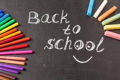 Zurück zu Schulhintergrund mit bunten Filzstiften und Titel zurück zu der Schule geschrieben durch weiße Kreide Lizenzfreies Stockbild