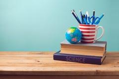 Zurück zu Schulkonzept mit Büchern, Bleistiften in der Schale und Kugel Lizenzfreie Stockfotografie