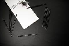 Zurück zu Schulkonzept mit Farbbleistiften, -Tintenfass und -notizblock auf schwarzem Hintergrund Stockbild