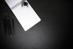 Zurück zu Schulkonzept mit Farbbleistiften, -Tintenfass und -notizblock auf schwarzem Hintergrund Lizenzfreies Stockfoto