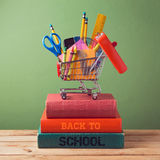 Zurück zu Schulkonzept mit Warenkorb auf Büchern Lizenzfreies Stockbild
