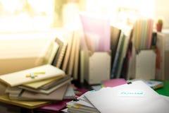 Zurückgewiesen; Stapel Dokumente Arbeiten oder Studieren am unordentlichen Schreibtisch stockfoto