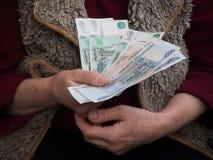 Zurückgezogen mit russischen Rubeln in seinen Händen Das Konzept der Sozialversicherung stockfotos