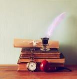 Zurückhaltendes Bild der weißen Feder, Tintenfaß, verzeichnen alte Bücher auf altem Holztisch in einer Liste Stockfoto
