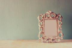Zurückhaltendes Bild des klassischen Rahmens der Weinleseantike auf Holztisch Gefiltertes Bild Lizenzfreie Stockbilder