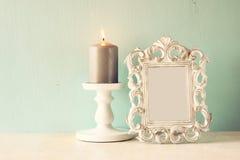 Zurückhaltendes Bild des klassischen Rahmens der Weinleseantike und brennende Kerze auf Holztisch Gefiltertes Bild Lizenzfreie Stockfotos