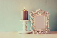 Zurückhaltendes Bild des klassischen Rahmens der Weinleseantike und brennende Kerze auf Holztisch Gefiltertes Bild Stockfotografie