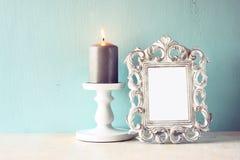 Zurückhaltendes Bild des klassischen Rahmens der Weinleseantike und brennende Kerze auf Holztisch Gefiltertes Bild Lizenzfreies Stockbild